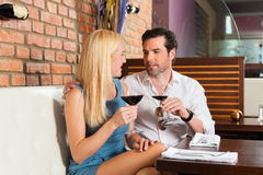 Couples attrayants buvant du vin rouge dans le bar Photo libre de droits