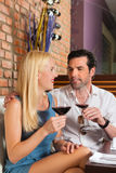 Couples attrayants buvant du vin rouge dans le bar Photographie stock libre de droits