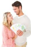 Couples attrayants clignotant leur argent liquide Images libres de droits
