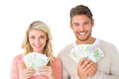 Couples attrayants clignotant leur argent liquide Images stock