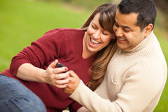Couples attrayants de chemin mélangé appréciant le téléphone intelligent Image stock