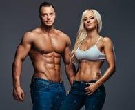 Couples attrayants de forme physique au-dessus de fond gris Photo stock