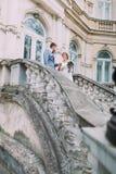 Couples attrayants de nouveaux mariés dans l'amour descendant par les escaliers antiques près du vieux palais autrichien Photographie stock