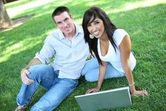 Couples attrayants en stationnement avec l'ordinateur portatif Photos stock