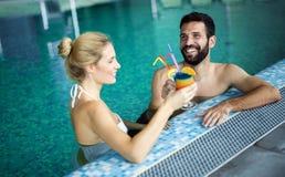Couples attrayants heureux détendant dans la piscine image stock
