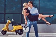 Couples attrayants heureux dans l'amour - le type élégant beau se tient sur des mains et embrasse son amie blonde avec du charme  Photo stock
