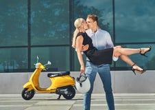 Couples attrayants heureux dans l'amour - le type élégant beau se tient sur des mains et embrasse son amie blonde avec du charme  Photographie stock libre de droits