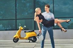 Couples attrayants heureux dans l'amour - le type élégant beau tient sur des mains son amie blonde avec du charme près d'un jaune Images stock