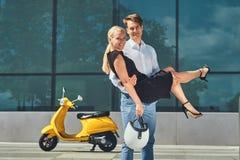 Couples attrayants heureux dans l'amour - le type élégant beau tient sur des mains son amie blonde avec du charme près d'un jaune Image libre de droits