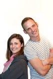 Couples attrayants heureux posant de nouveau au dos Photos stock