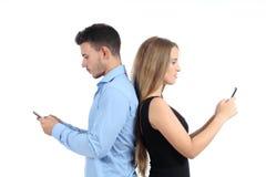 Couples attrayants introduisant au clavier leurs téléphones portables Photo stock