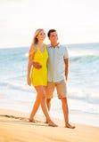 Couples attrayants jouant sur la plage au coucher du soleil Photographie stock libre de droits