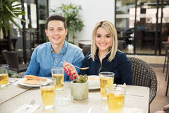 Couples attrayants mangeant dans un restaurant Photographie stock