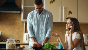Couples attrayants pendant le début de la matinée de cuisine Téléphone de causerie de belle fille tandis que son ami faisant cuir Photographie stock