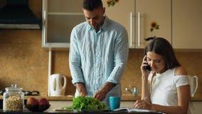 Couples attrayants pendant le début de la matinée de cuisine Téléphone de causerie de belle fille tandis que son ami faisant cuir Images stock