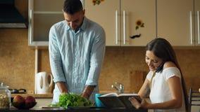 Couples attrayants pendant le début de la matinée de cuisine Téléphone de causerie de belle fille tandis que son ami faisant cuir Photo stock