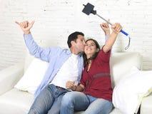Couples attrayants prenant la photo de selfie ou tirant la vidéo d'individu avec le téléphone portable et le bâton reposant à la  Photos libres de droits