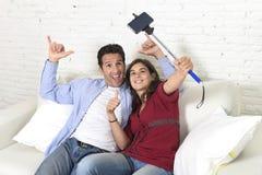 Couples attrayants prenant la photo de selfie ou tirant la vidéo d'individu avec le téléphone portable et le bâton reposant à la  Photographie stock