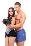 Couples attrayants s'exerçant avec un poids Photo libre de droits
