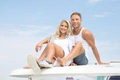 Couples attrayants se reposant sur le bateau à voile - amour. Image stock