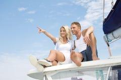 Couples attrayants se reposant sur le bateau à voile - amour. Images stock