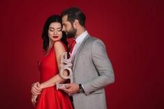 Couples attrayants se tenant avec amour de signe Photos stock