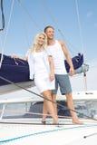 Couples attrayants se tenant sur le bateau à voile - voyage de navigation. Image libre de droits