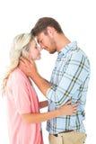 Couples attrayants souriant à l'un l'autre et à étreindre Photos stock
