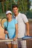 Couples attrayants souriant sur le court de tennis Photos libres de droits