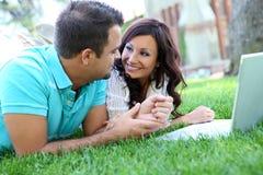 Couples attrayants sur l'herbe avec l'ordinateur Photos libres de droits