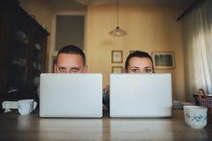 Couples attrayants utilisant l'ordinateur portable ensemble sur le sofa à faire des emplettes en ligne a photographie stock libre de droits