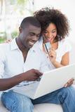 Couples attrayants utilisant l'ordinateur portable ensemble sur le sofa à faire des emplettes en ligne Image libre de droits