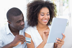 Couples attrayants utilisant le comprimé ensemble sur le sofa à faire des emplettes en ligne Image libre de droits