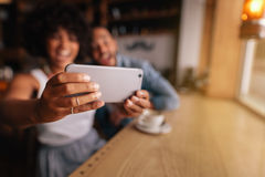 Couples au café prenant l'autoportrait avec le téléphone intelligent Photographie stock