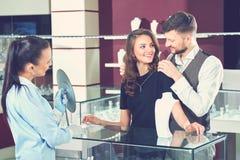 Couples au collier de choix et de essai de magasin de bijoux image stock