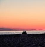 Couples au coucher du soleil de observation de plage Photographie stock libre de droits