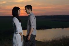 Couples au coucher du soleil et au lac Image libre de droits