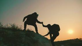 couples augmentant l'aide silhouette en montagnes Les couples de travail d'?quipe augmentant, s'aident, font confiance ? l'aide,  clips vidéos