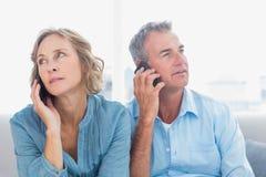 Couples austères à leurs téléphones portables sur le divan Photographie stock