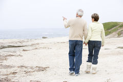 Couples aux mains et au pointage de fixation de plage Photographie stock