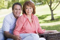 Couples aux mains et au sourire d'une exploitation de pique-nique Photographie stock libre de droits