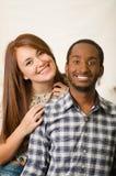 Couples avec du charme interraciaux portant les vêtements sport posant l'interaction fond amical et blanc de studio Images stock