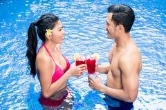 Couples ayant des boissons dans la piscine en Asie Photos stock