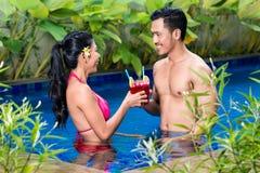 Couples ayant des boissons dans la piscine en Asie Image libre de droits