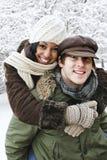 Couples ayant l'amusement à l'extérieur en hiver Photographie stock