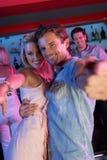 Couples ayant l'amusement dans le bar occupé Photographie stock