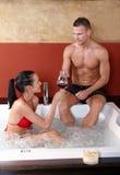 Couples ayant l'amusement dans le jacuzzi Photos stock