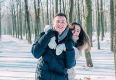 Couples ayant l'amusement dans le parc neigeux Photo stock