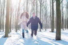 Couples ayant l'amusement dans le parc neigeux Photos libres de droits
