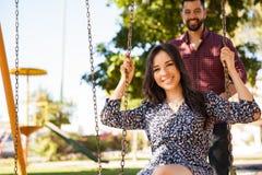 Couples ayant l'amusement dans une oscillation Photos stock